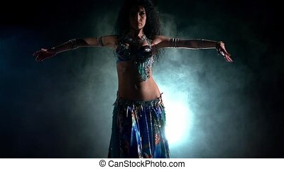 Beautiful young belly dancer, modern, on black, blue, smoke, slow motion