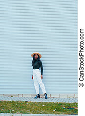 Beautiful young black african girl in white jeans and a hat with a happy smile on the street of the blue wall of the building. Fashion colors
