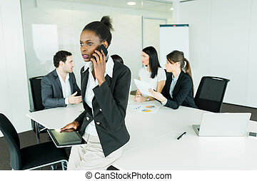 Beautiful, young, black businesswoman holding a tablet at an office meeting and getting bad news on the phone