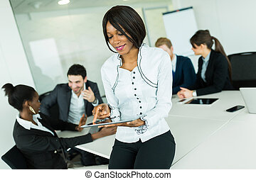 Beautiful, young, black businesswoman looking at a tablet at an office meeting