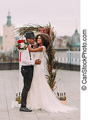 Beautiful young black wedding couple dreamily looks into the sky