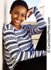 Beautiful young black woman smiling outside