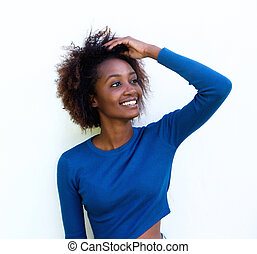 Beautiful young black woman smiling with hand in hair