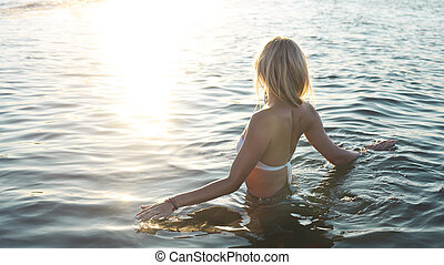 Beautiful young blond girl relaxing on a beach of tropical ocean