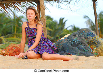 Beautiful young blond girl sitting on beach