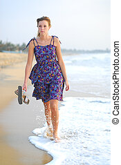 Beautiful young blond girl walking on beach