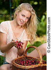 Beautiful young blond woman harvesting cherries on a hot spring sunny day in cherry plantation