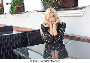 Beautiful young blond woman in a cafe with a mobile phone