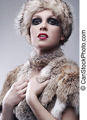beautiful young blond woman in fur, studio shot