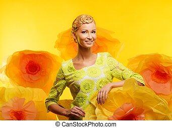 Beautiful young blond woman in green dress among big yellow flowers