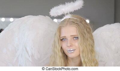 Beautiful young blond woman posing at camera