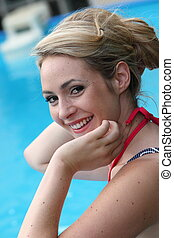 Beautiful young blond woman swimming in a pool