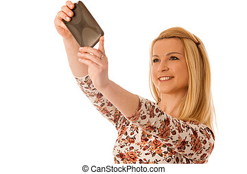 Beautiful young blond woman taking selfie isolated over white background