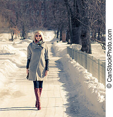 Beautiful young blond woman walking in the park in winter afternoon in coat and red boots, sunglasses.