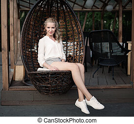 Beautiful young blond woman with long legs sitting in a wicker chair at an outdoor cafe on a warm summer evening, smiling and looking in camera