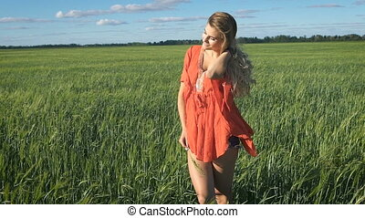 Beautiful young blond woman with the happy look standing and enjoying herself at a green field