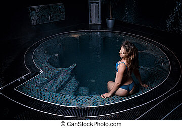 Beautiful young blonde caucasian woman in bikini relaxing in hot pool or jacuzzi at spa center
