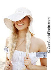 Beautiful young blonde girl in hat on the beach