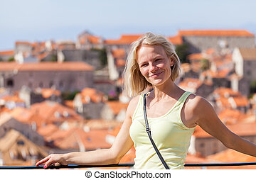 Beautiful young blonde girl on a background of blurred panoramic cityscape. Dubrovnik