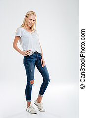 Beautiful young blonde girl putting smartphone in the jeans pocket