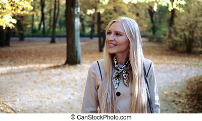 Beautiful young blonde girl walking in the park in autumn