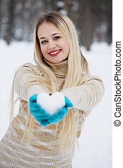 blonde girl with a heart made of snow in her hands