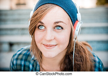 beautiful young blonde hipster woman listening music in...