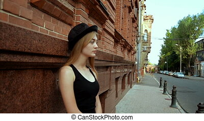 beautiful young blonde in a black hat stands on a street