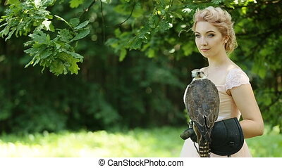 Beautiful young blonde in pink dress with a falcon in hands looking