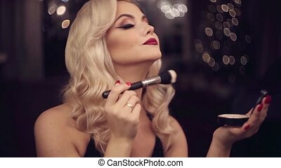 Beautiful young blonde makes a bright holiday makeup....