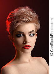 Beautiful young blonde red lipped woman posing in artistic red l