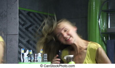 Beautiful young blonde woman dries her long hair with a hair dryer and sings. Instead of a microphone hairbrush.