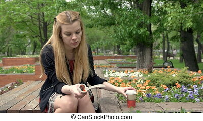 Beautiful young blonde woman drinking coffee and reading a book in summer park
