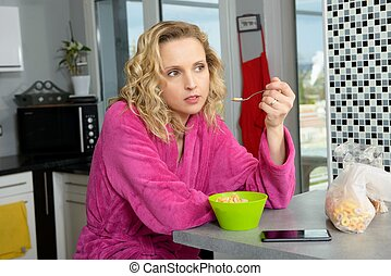 young blonde woman eating cereals in the morning