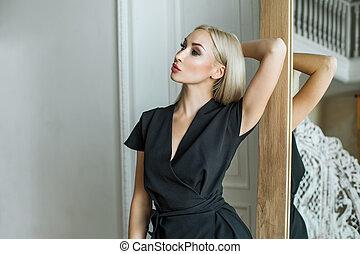 Beautiful young blonde woman in black dress posing