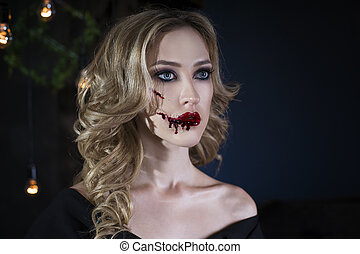 Beautiful young blonde woman in black dress with halloween...