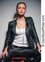 beautiful young blonde woman in leather clothes sitting on stool