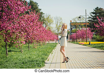 Beautiful young blonde woman in white dress walking at spring park with pink cherry trees