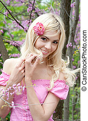 Beautiful young blonde woman outdoor portrait in spring park