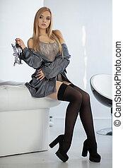 Beautiful young blonde woman posing sitting