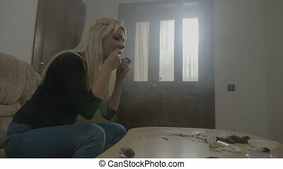 Beautiful young blonde woman rolling a marijuana cigarette...