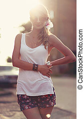 Beautiful young blonde woman standing on the beach. Wearing white T-shirt. Wind is blowing into her long blonde hair. In the background is sunset and warm feeling
