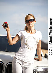 Beautiful young blonde woman with car key in hand