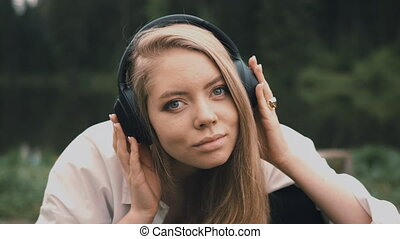 Beautiful young blonde woman with natural appearance listening to music on black headphones