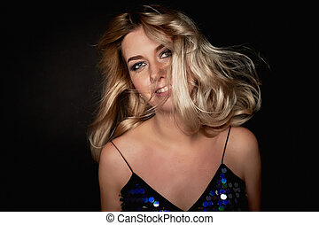 Beautiful young blonde woman with professional makeup Smokey eyes.Hair fluttering in dance