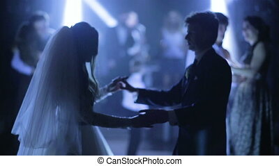 Beautiful young bride and a groom dancing in their wedding ceremony.