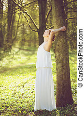 Beautiful young bride in white wedding dress leaning against tree outdoors