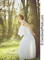 Beautiful young bride in white wedding dress standing outdoors