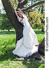 beautiful young bride leaned against a tree in the park