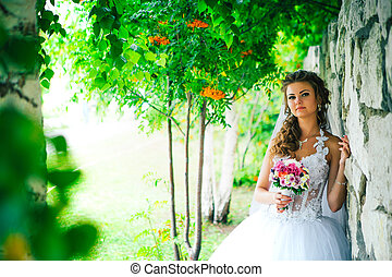 Beautiful young bride standing on a stone wall background